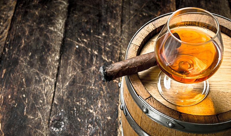 Viele Rum-Fans genießen die edlen Tropfen am liebsten mit einer guten Zigarre.