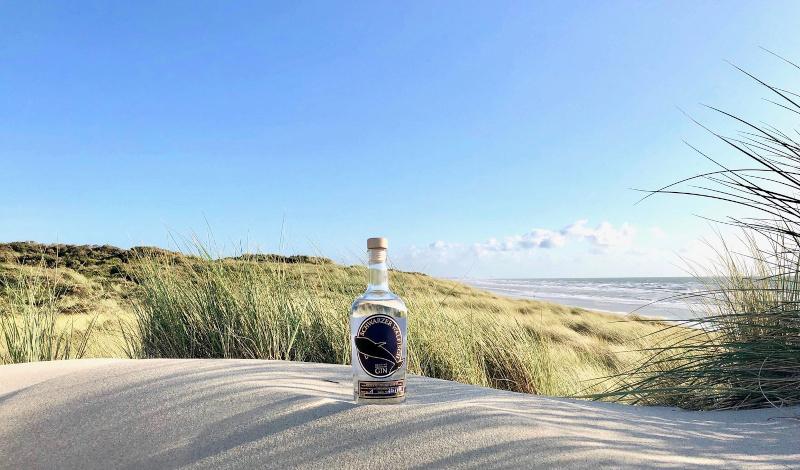 Schwarzer Walfisch Gin am Meer im Sand